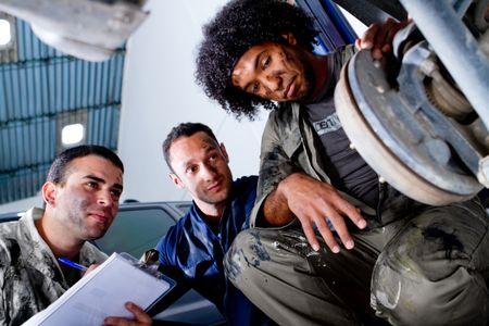 Mechanics fixing a car at the garage
