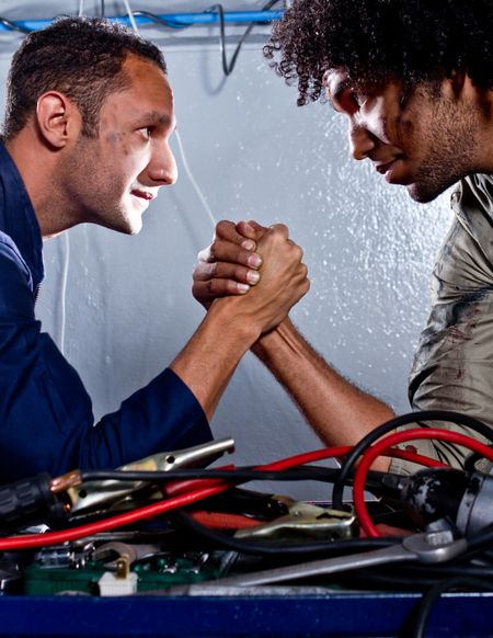 Two strong mechanics in a garage arm-wrestling