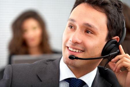 male customer service representative smiling in an office
