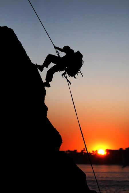 rock climber at sunset time going up a mountain