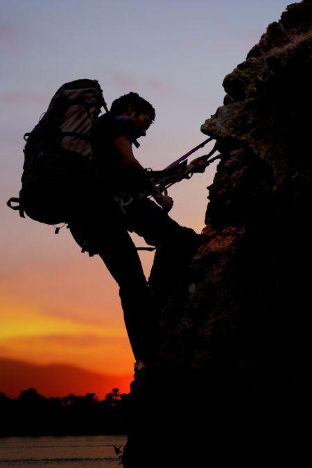 rock climber at sunset time going up a mountain