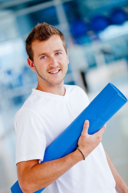 Handsome athletic man at the gym with a mat