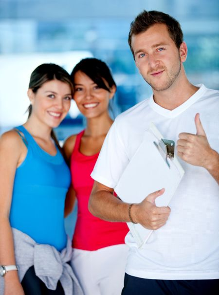 Trainer smiling with two beautiful women at the gym