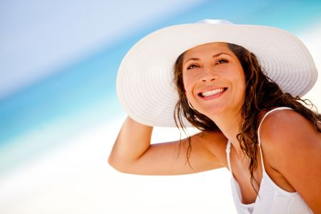 Beautiful woman at the beach wearing a hat and smiling