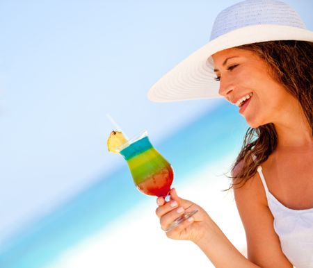 Happy woman enjoying a tropical cocktail at the beach