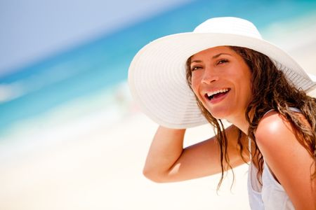 Happy woman at the beach wearing a hat on a summer day