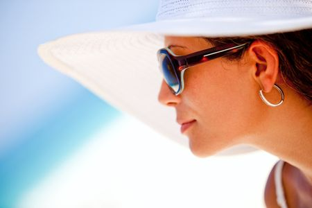 Summer woman looking at the horizon, wearing hat and sunglasses