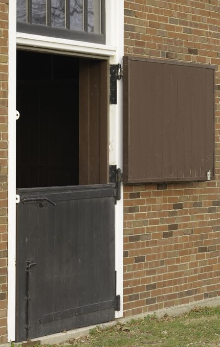 Dutch door to Colonial-style brick horse stable, with top half open