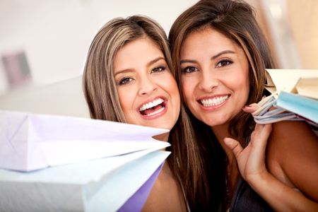 Happy shopping women smiling at a retail store with bags