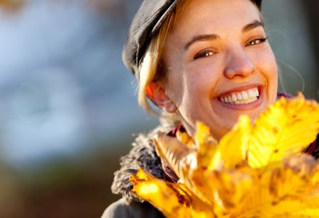 Happy autumn woman holding leaves and smiling outdoors