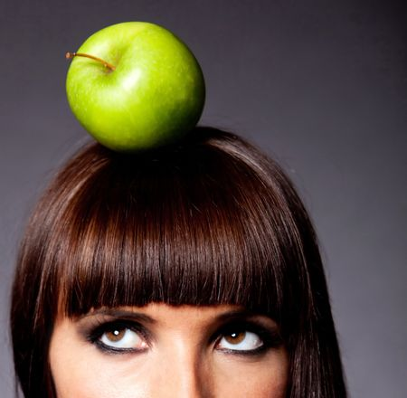 Woman thinking on a healthy diet with an apple on her head