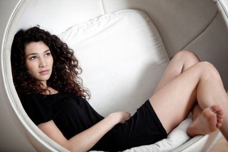 Beautiful woman sitting on a chair daydreaming