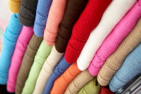 colourful clothes stacked in a retail store - woolen jumpers