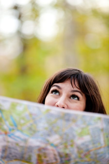 Woman exploring outdoors holding a map and looking lost