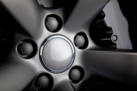 Picture of a black car tire with focus on nuts