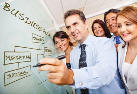 Corporate group drawing a business plan on the board
