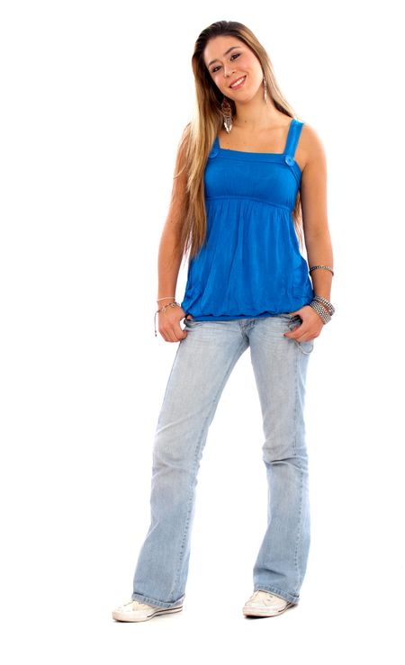 casual girl standing up and smiling wearing jeans and a blue top - isolated over a white background
