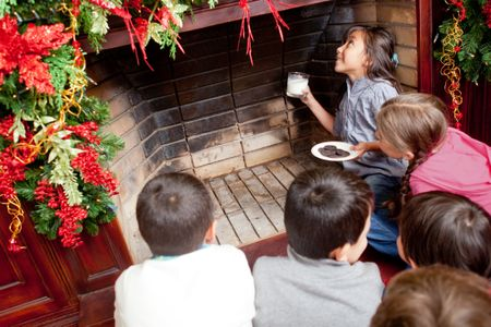 Kids waiting for Santa by the chimney with milk and cookies