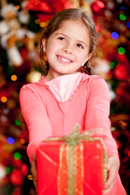 Beautiful girl holding a Christmas gift and smiling at home