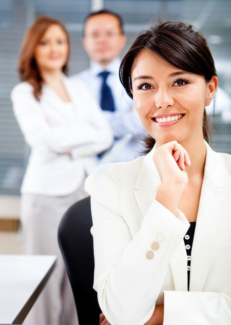 Successful woman with a business team looking confident