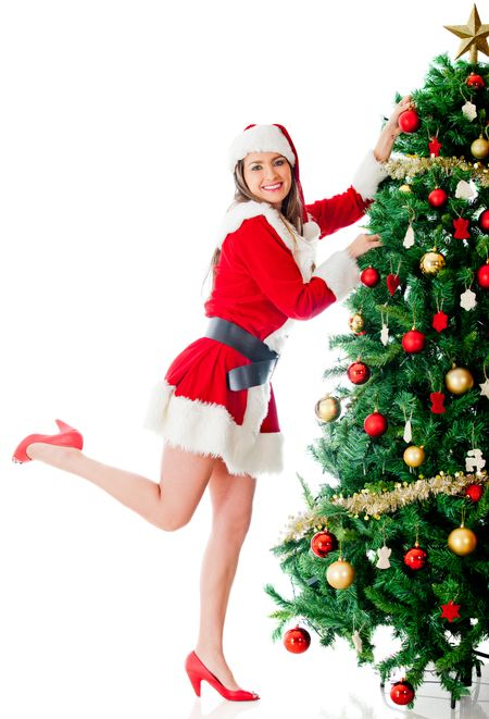 Female Santa decorating the Christmas tree with ornaments
