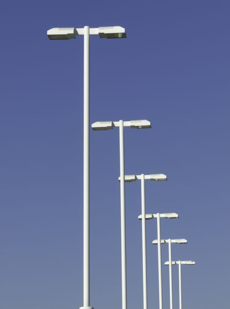 Row of tall white lampposts over parking lot, with background of blue sky