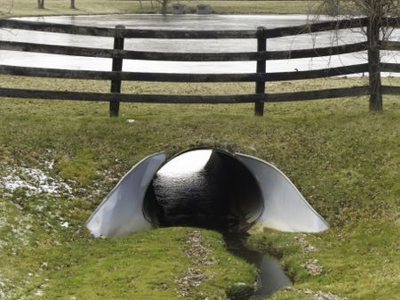 Landscaper's solution to prevent flooding from rain or snowmelt: Steel culvert with collar by wooden fence near pond in mid December