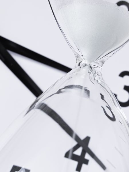 Time running out: White sand falling inside hourglass, with analog clock in background (focus on neck of hourglass), shallow depth of field