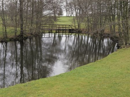 Public golf course on a winter day without snow, northern Illinois: Bend in stream reflecting bare trees by footbridge