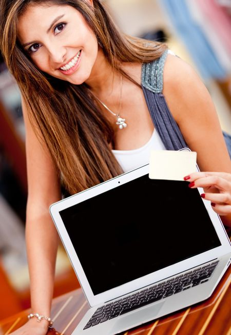 Woman holding a credit card and a laptop for online shopping