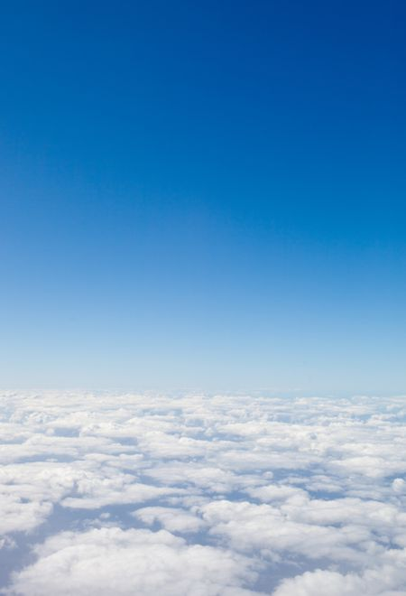 Beautiful blue sky seen from an airplane with clouds at the bottom