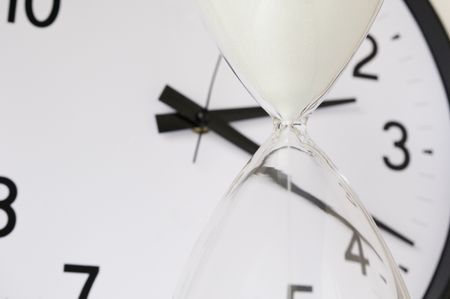 Two measurements of time: White sand falling inside hourglass, with round analog clock in  background (focus on neck of hourglass), shallow depth of field
