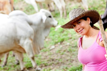 Cowgirl portrait in a farm with cattle at the background