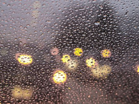 Abstract of rain at rush hour: Raindrops all over windshield (selective focus)
