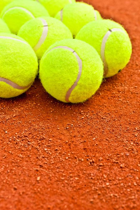 Close-up of tennis balls on a clay court