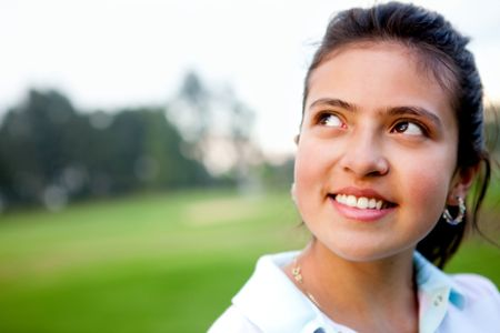Portrait of a pensive young woman outdoors smiling