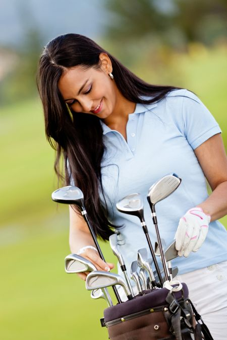 Female golf player with a bag at the course