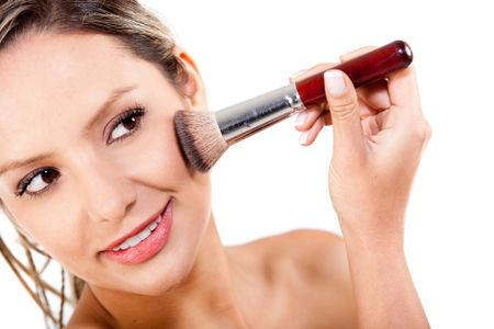 Woman applying rouge with a make up brush - isolated over a white background