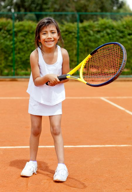 Girl playing tennis holding a racket at the court