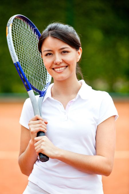 Woman playing tennis holding a racket and smiling