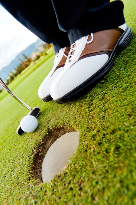 Golf player hitting the ball close-up on hole