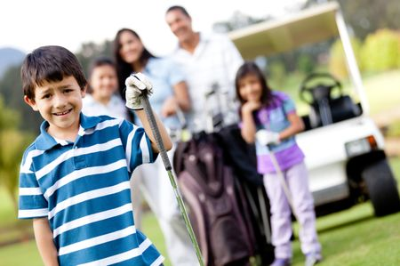Boy playing golf with his family at the background