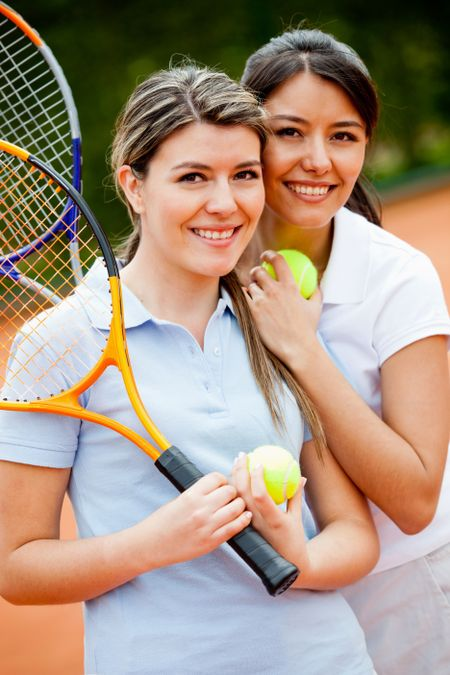 Beautiful female tennis players at the court smiling