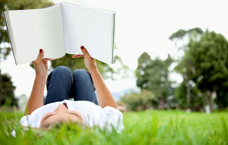 Woman lying down outdoors reading a book