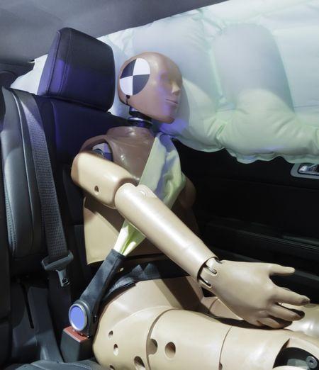 Automotive crash test dummy strapped into car seat, head against air bag