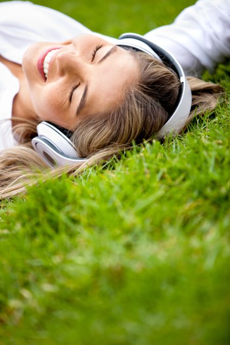 Girl lying at the park relaxing with music