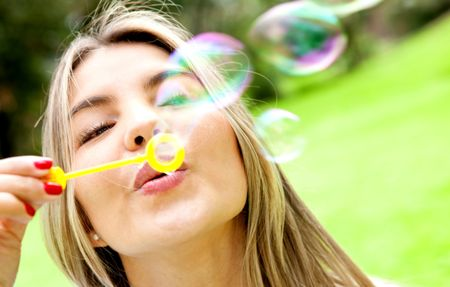 Woman blowing soap bubbles with a wand at the park