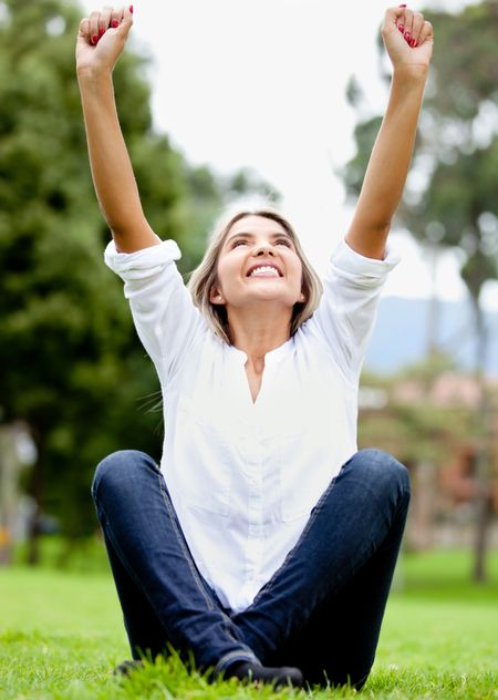 Happy woman outdoors with arms up and smiling