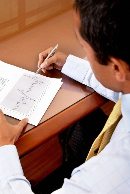 business man writing on a financial report where you can see the company growth