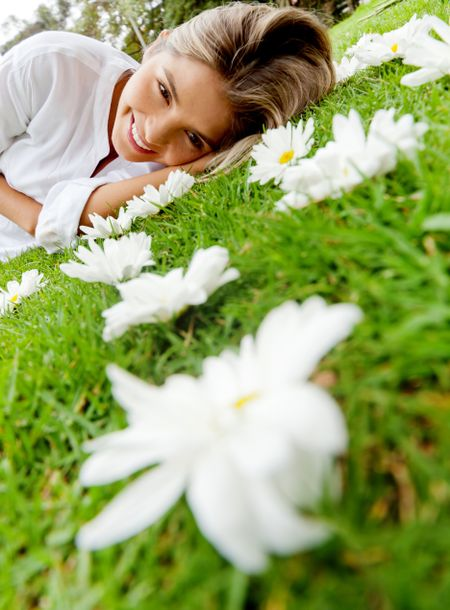 Beautiful woman lying on a floral garden full of daisies